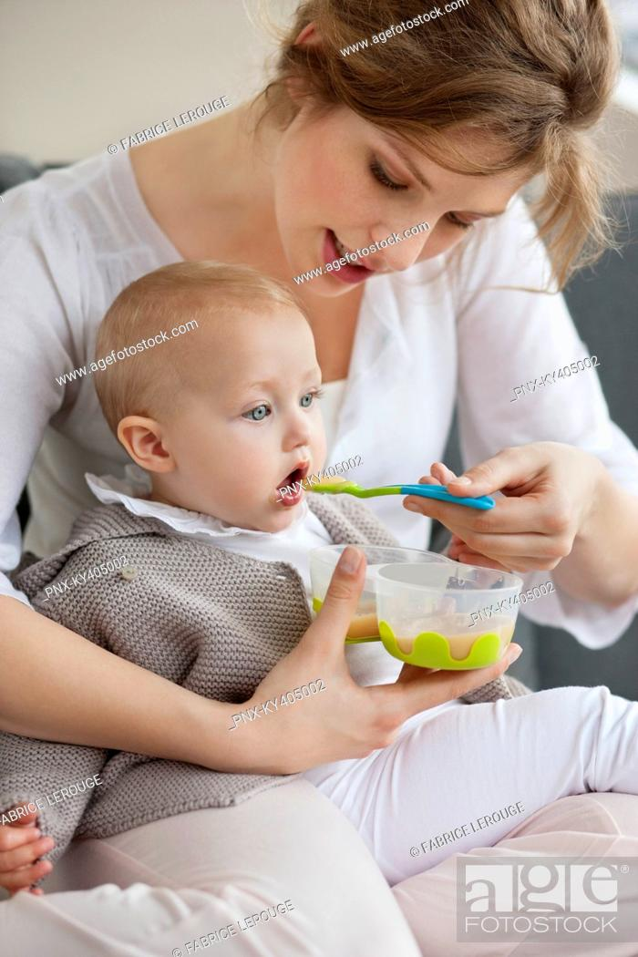 Stock Photo: Woman feeding her daughter.