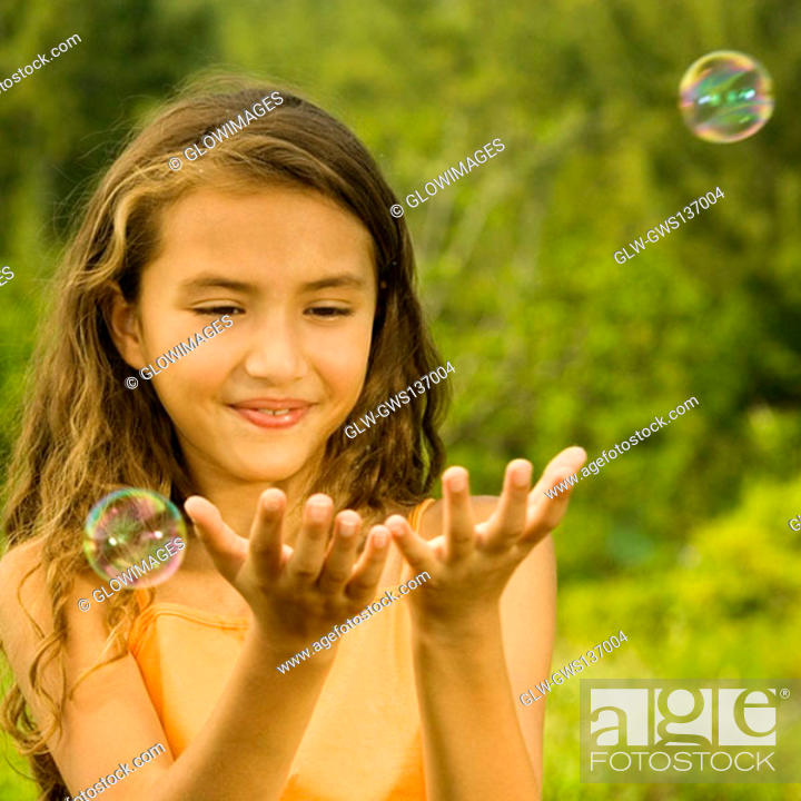 Stock Photo: Close-up of a girl catching bubbles.