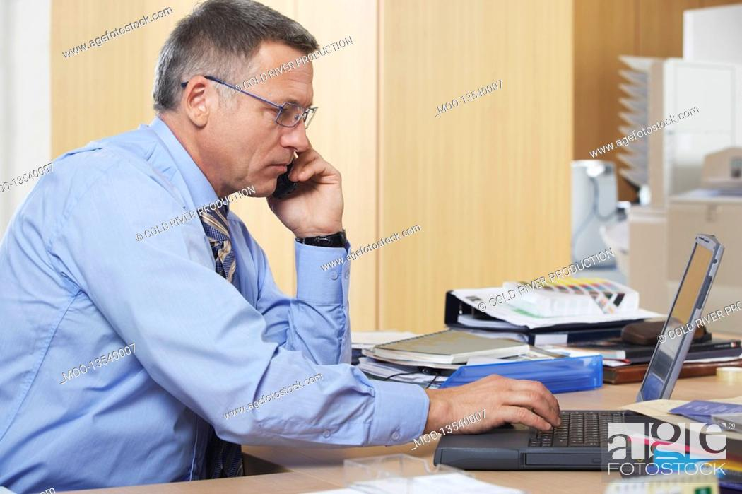 Stock Photo: Businessman talking on mobile phone using laptop in office.