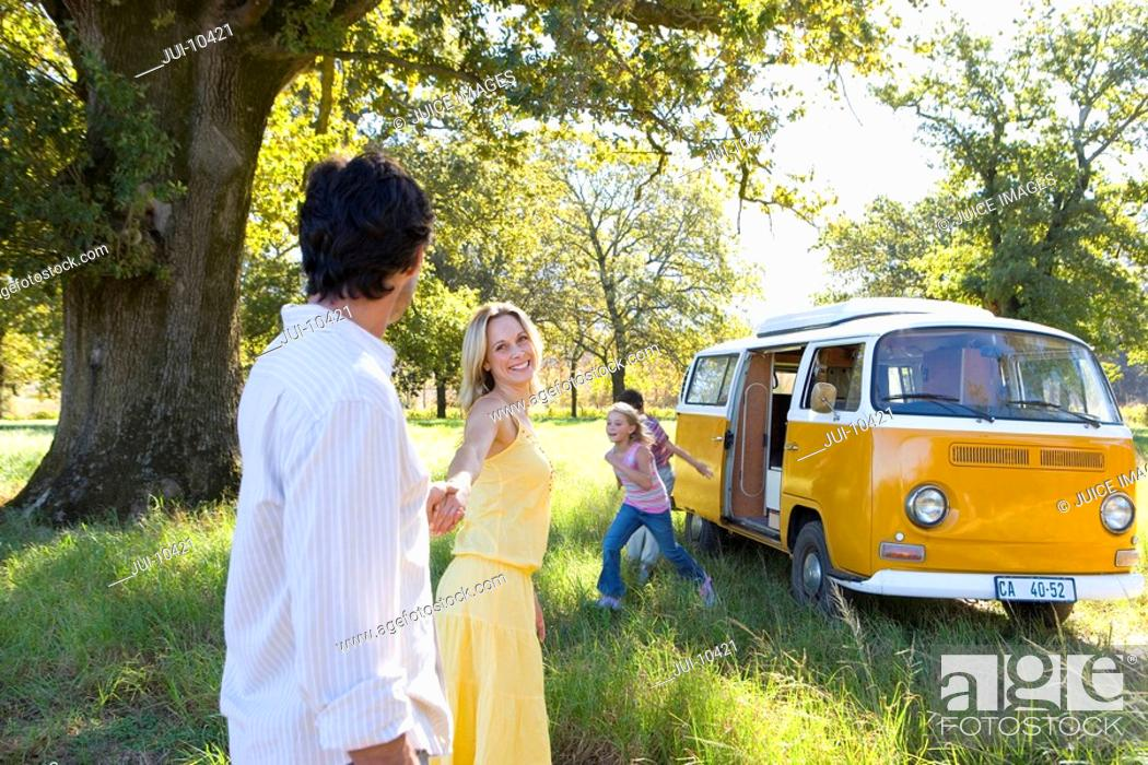 Stock Photo: Family of four by camper van in field, woman leading man by hand, smiling, side view.