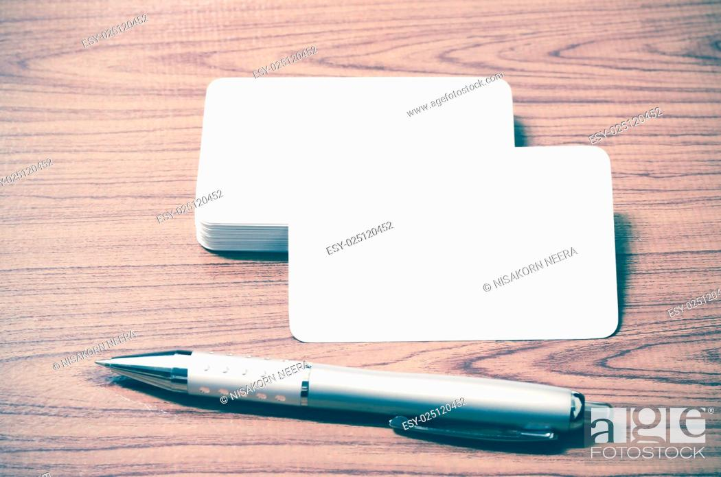 Stock Photo: stack of business card with pen on wood background vintage style.