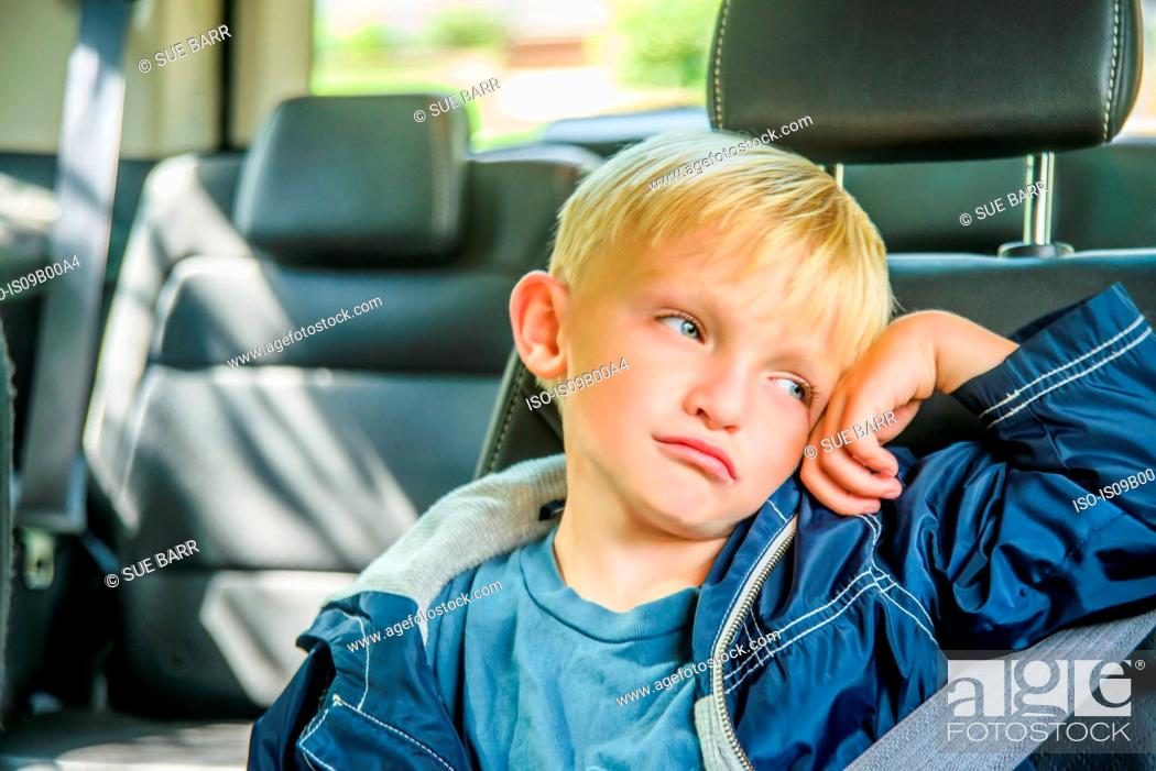 Stock Photo: Young boy sitting in back of vehicle, bored expression.