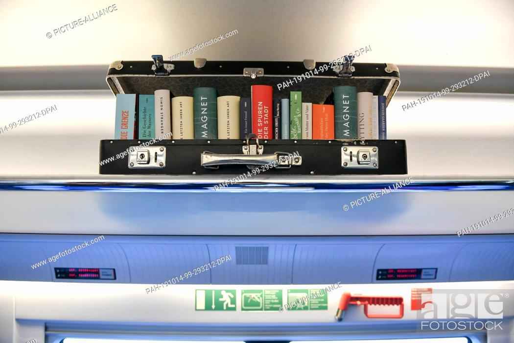 Stock Photo: 14 October 2019, Berlin: Books can be seen in the literature train on its way from Berlin to Cologne in a suitcase lying on the luggage rack.
