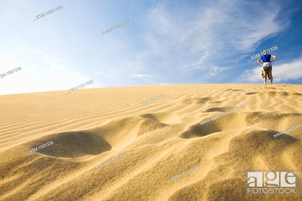 Stock Photo: Woman at the top of a sand dune with her footprints in the foreground.