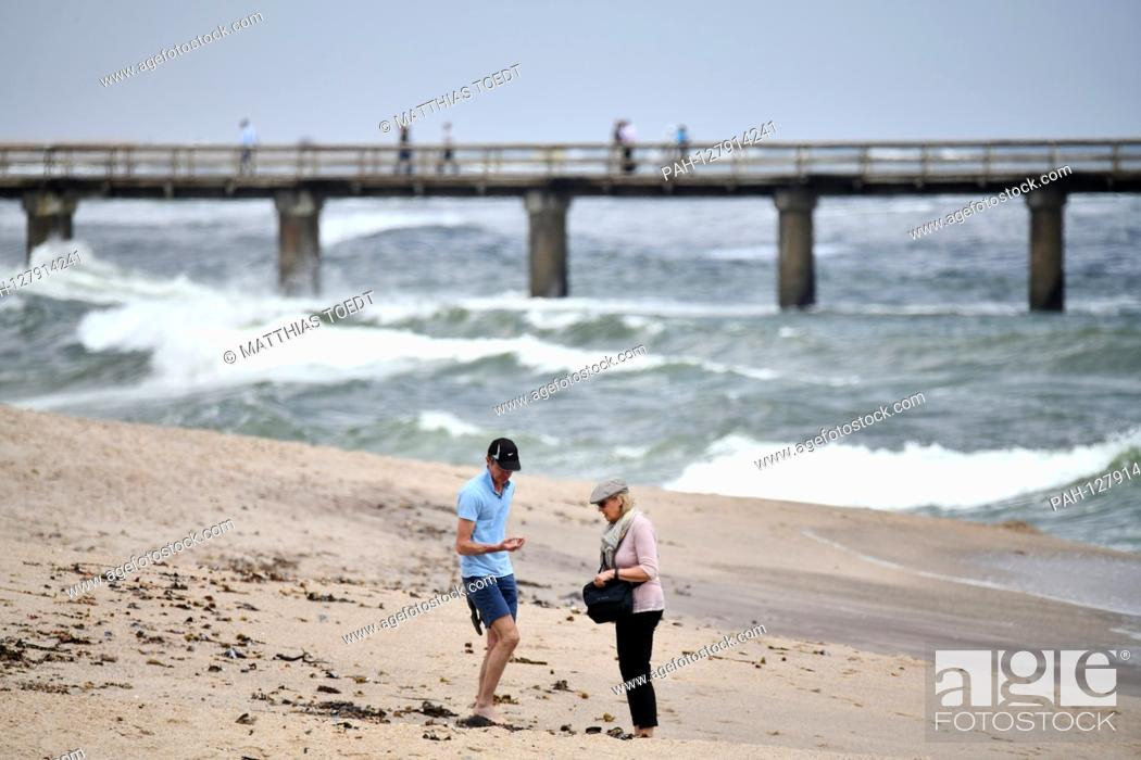 Stock Photo: Two walkers in front of the pier in Swakopmund collect shells on the Atlantic beach, taken on 02.03.2019. Photo: Matthias Toedt / dpa-Zentralbild / ZB / Picture.