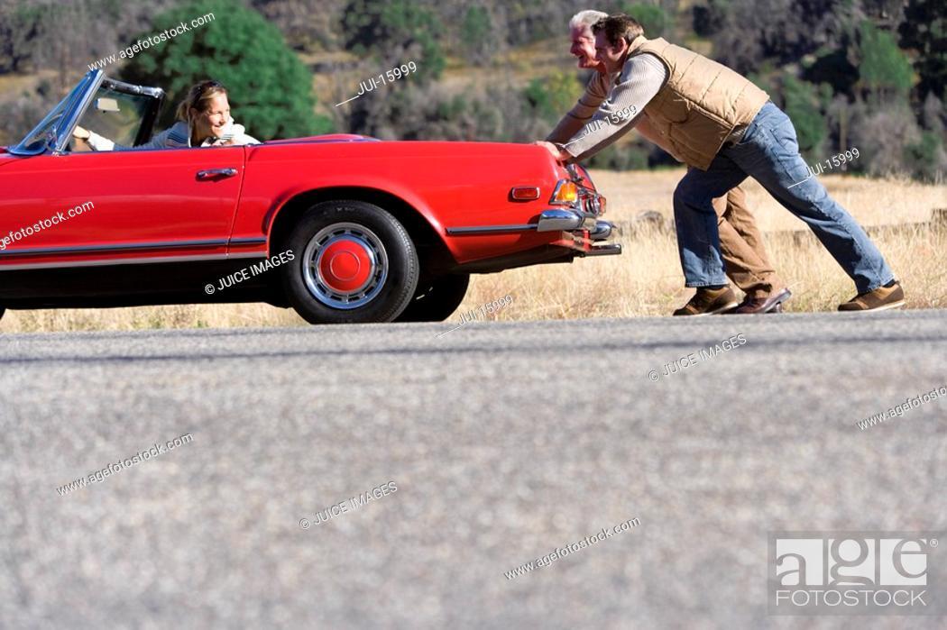 Stock Photo: Men pushing convertible that has broken down.