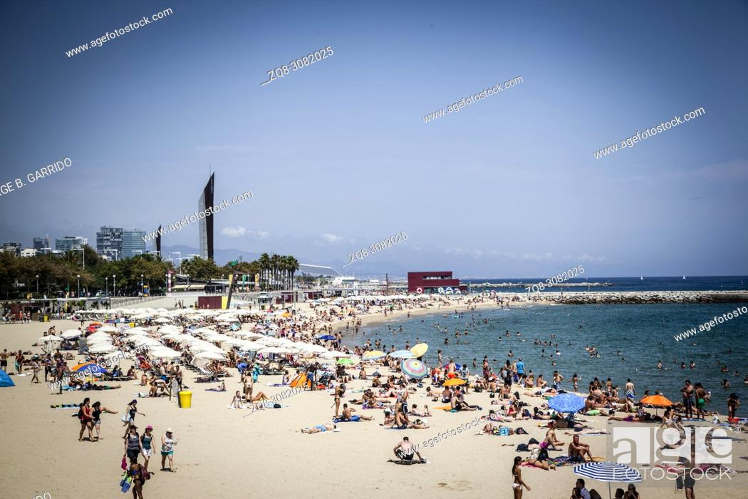 Stock Photo: Tourists sunbathe at Barceloneta beach on a hot summer day.