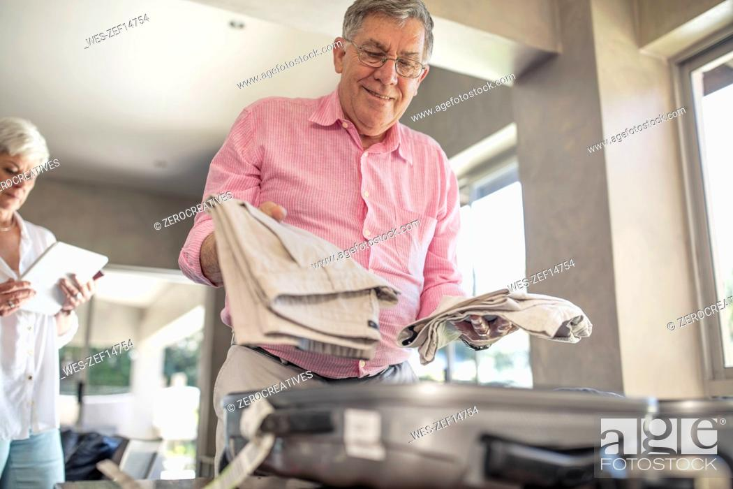 Stock Photo: Senior man packing for a trip.