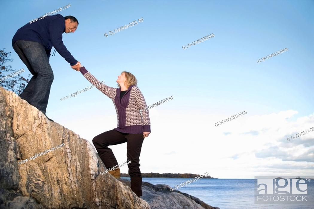 Stock Photo: Mature man helping a mature woman to climb a rock.
