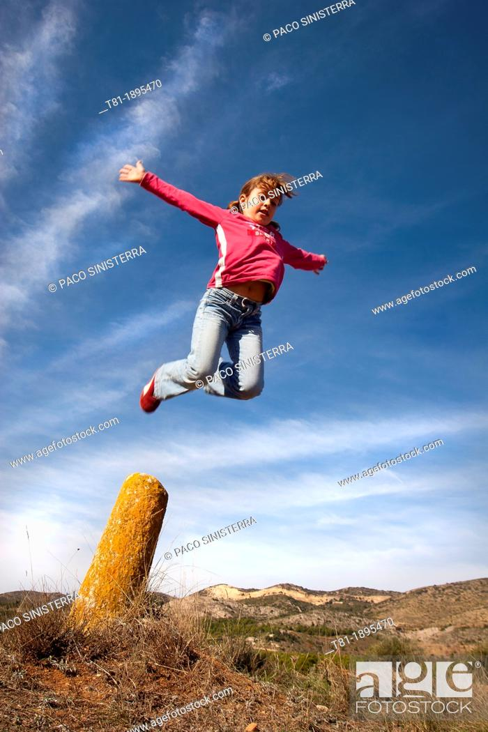 Stock Photo: Girl jumping in the blue sky.