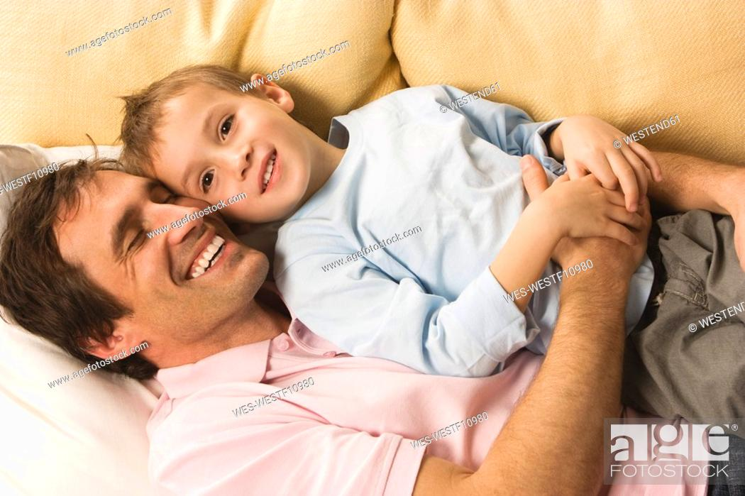 Stock Photo: Father and son 4-5, relaxing on sofa, elevated view.