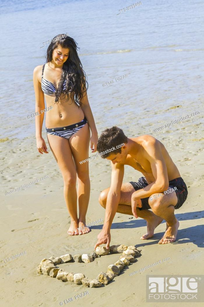 Imagen: Young couple on beach forming symbolic heart from group of stones.