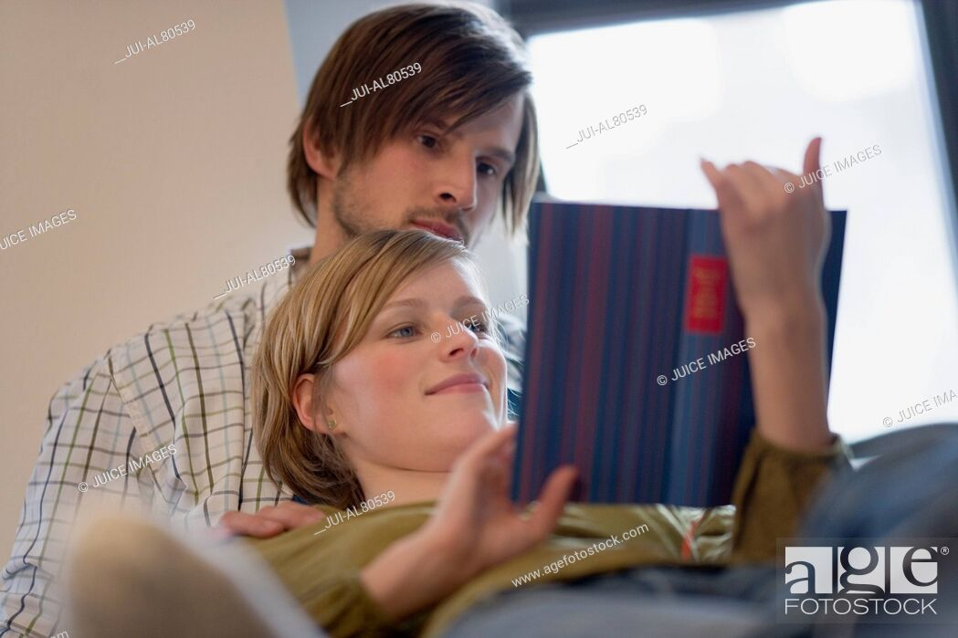 Stock Photo: Young couple laying together and reading.