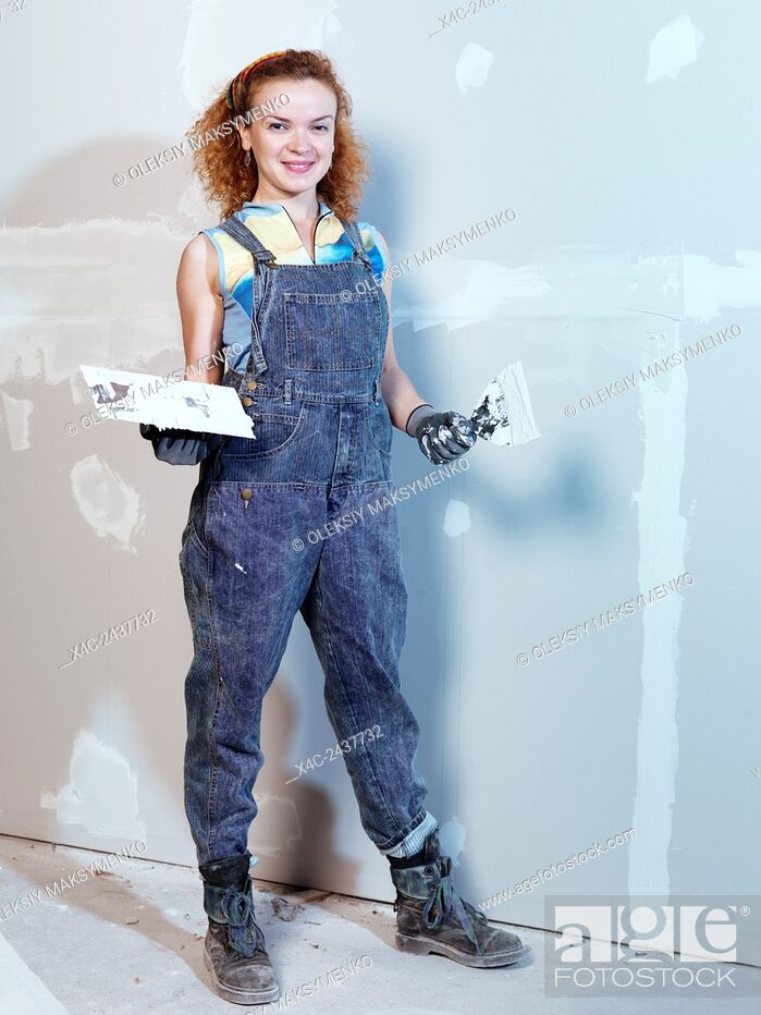 Stock Photo: Portrait of a smiling young woman construction worker with a trowel and putty knife patching up drywall.