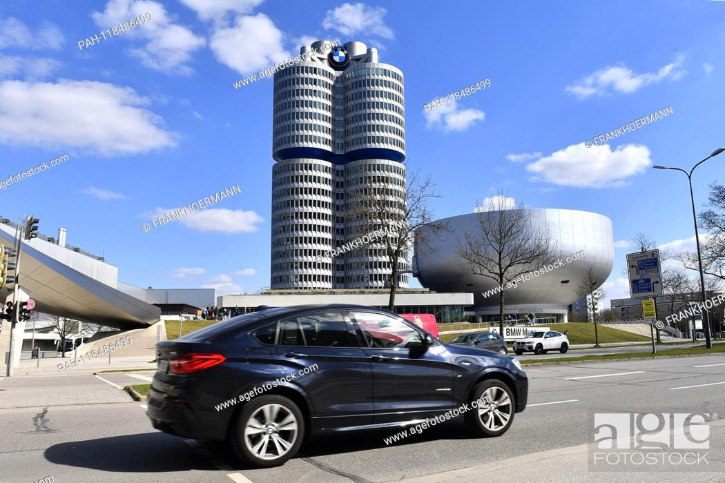 A BMW X4 car, driving past the corporate headquarters in