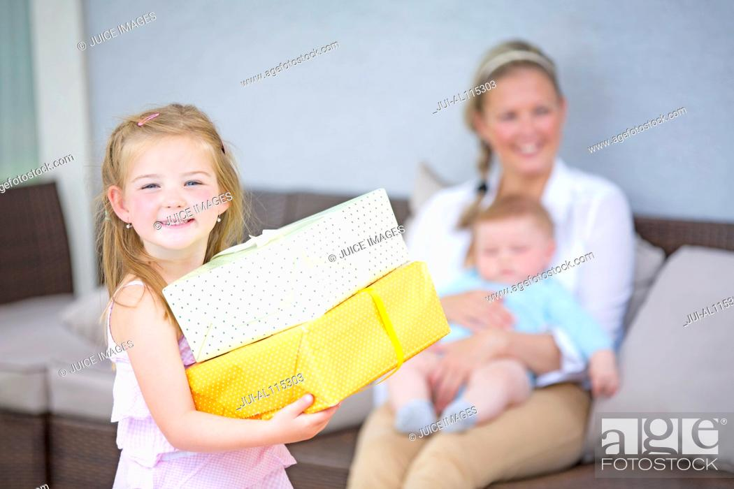 Stock Photo: Girl holding gifts with baby boy and mother in background.
