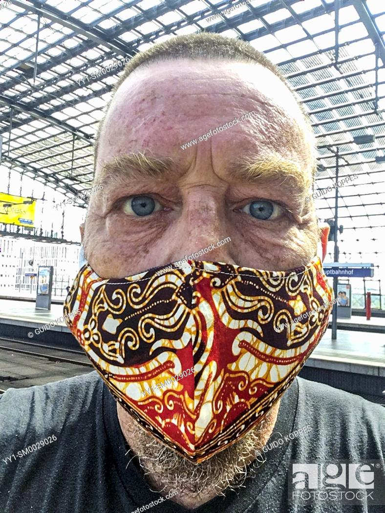 """Stock Photo: Berlin, Germany. Sefie of a mature adult male with Corona Haridue wearing a """"""""protective"""""""" facemask."""