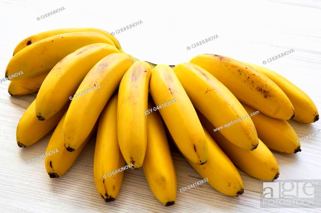 Stock Photo: Bunch of baby banana on a white wooden background. Closeup.