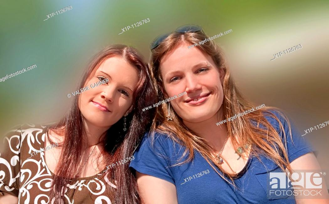 Stock Photo: This stock photo are two young adult Caucasian brunette women both with long hair and smiling who are both sisters and friends They are in their early twenties.