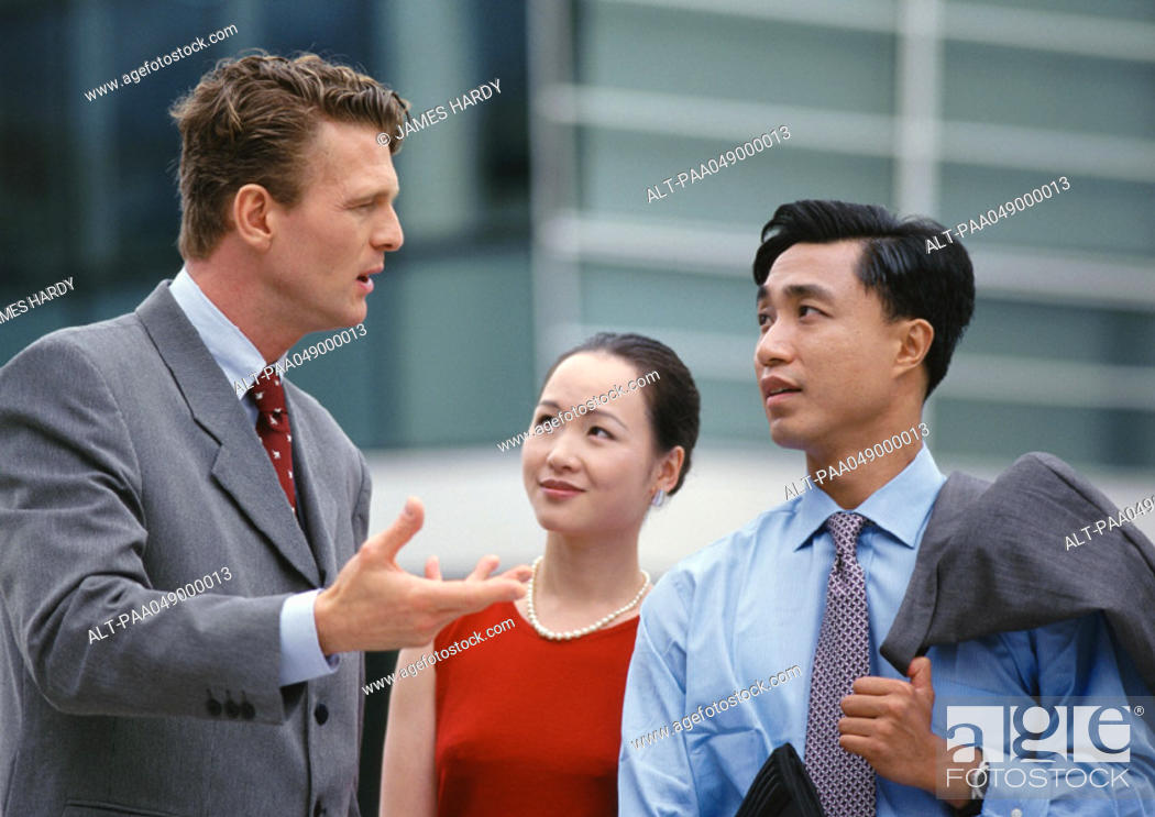Stock Photo: Two men and a woman, one gesturing with hand.