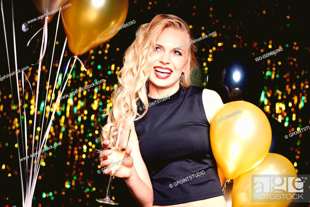 Stock Photo: Portrait of young woman at party, holding champagne glass.