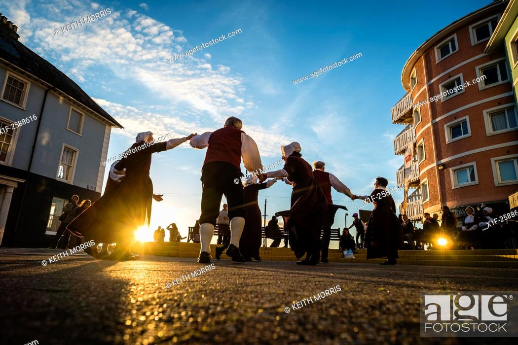 Stock Photo: A group of people in traditional costume folk dancing on Aberystwyth promenade at sunset, August evening, summer 2015.