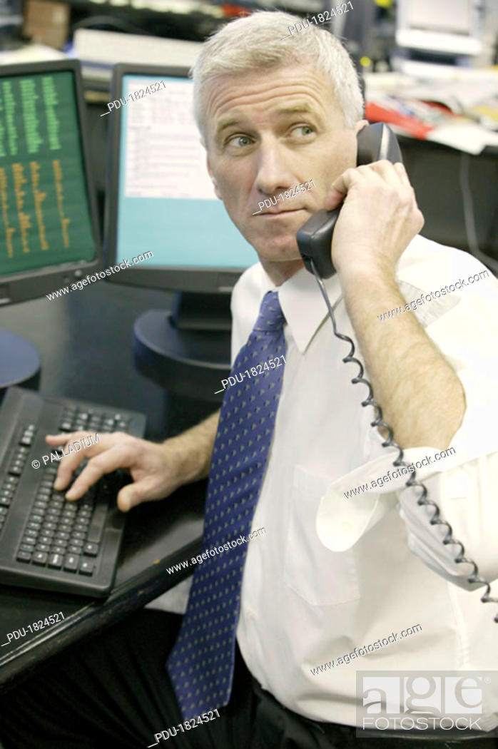 Stock Photo: Businessman at computer talking on phone.