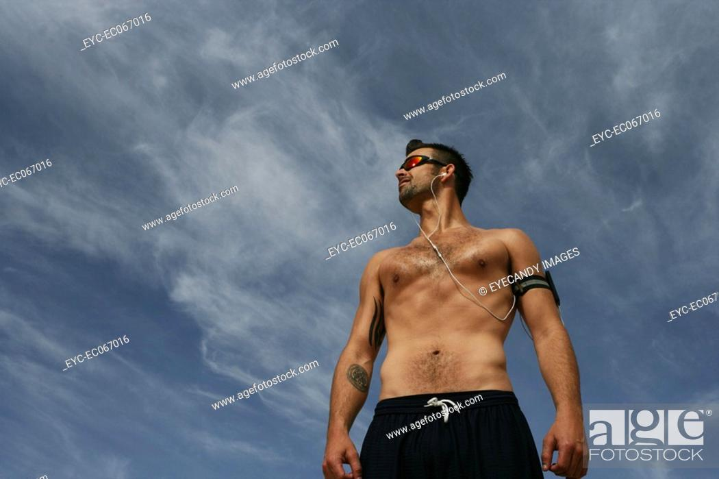 Stock Photo: Caucasian man standing outdoors shirtless listening to music.