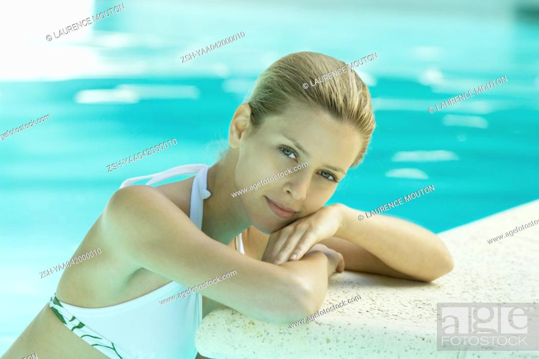 Stock Photo: Young woman in pool, leaning against edge of pool.