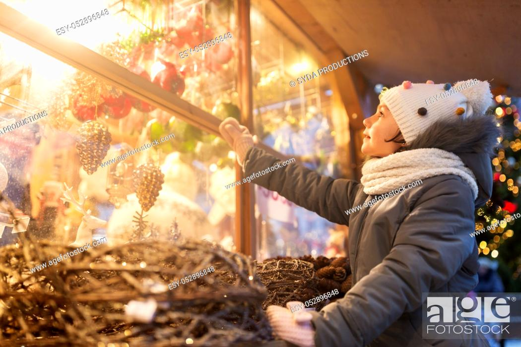 Stock Photo: girl choosing christmas decorations at market.