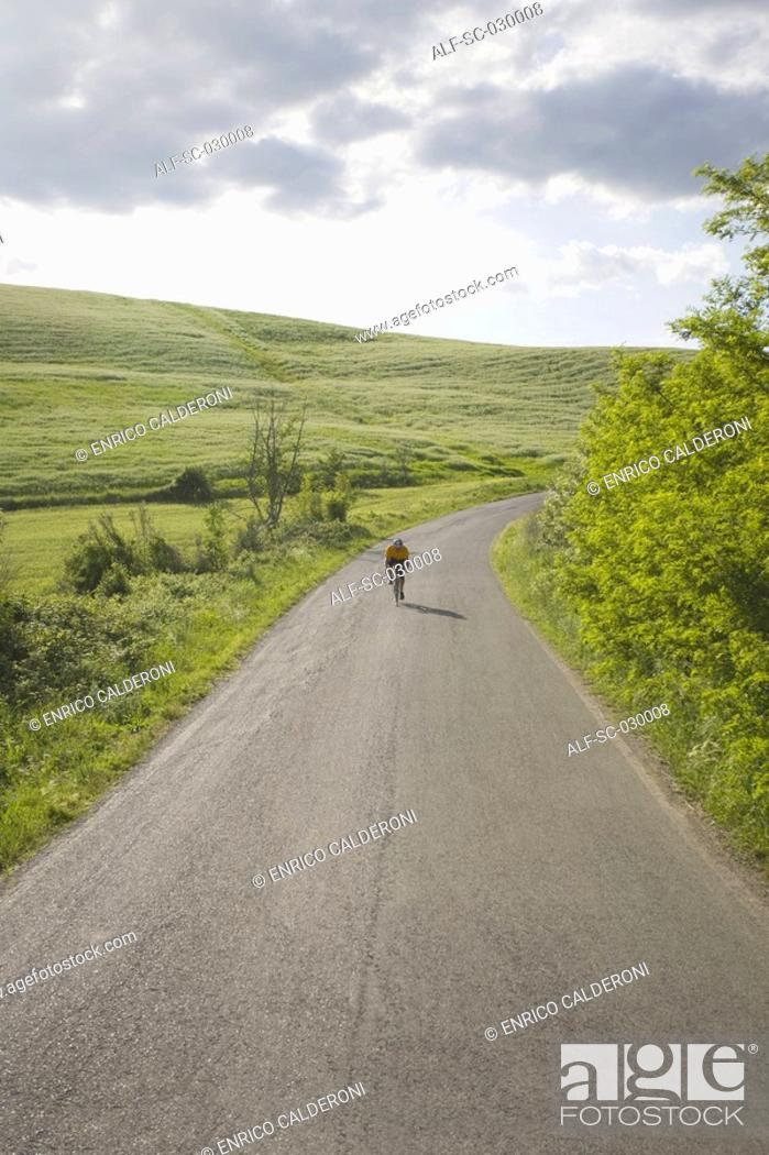 Stock Photo: Cyclist on road through hills.