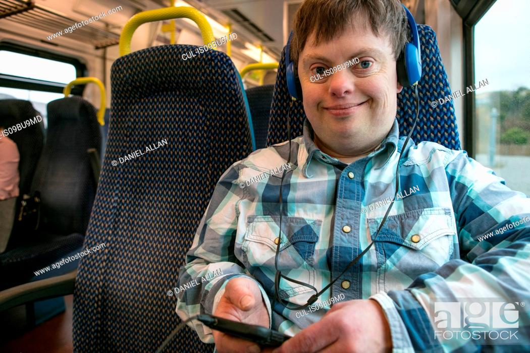 Stock Photo: Man with down syndrome with using headphones and cell phone on train.