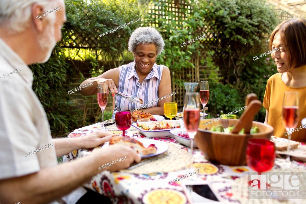 Photo de stock: Senior friends enjoying lunch at patio table.