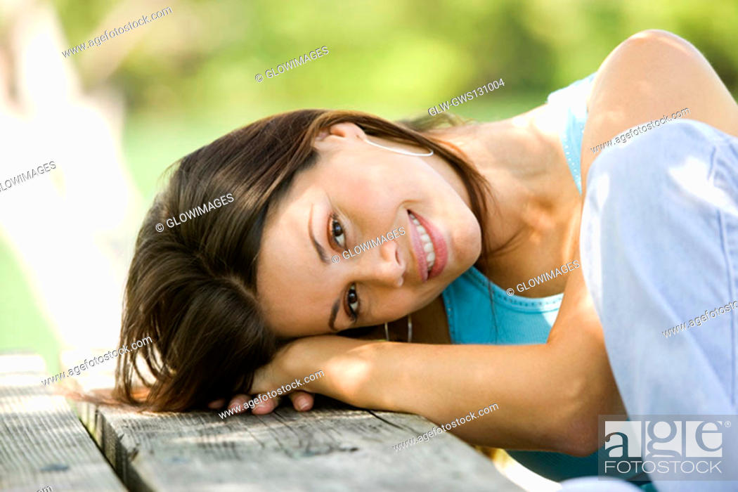 Stock Photo: Portrait of a young woman resting on a bench.