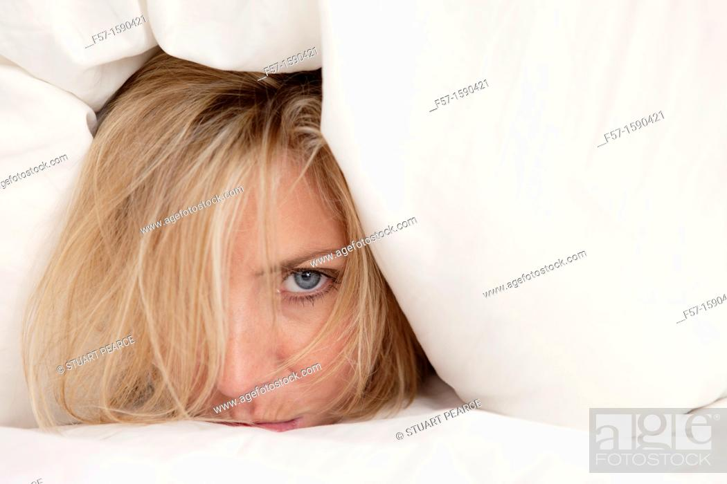Stock Photo: Young woman in bed with pillow on her head.
