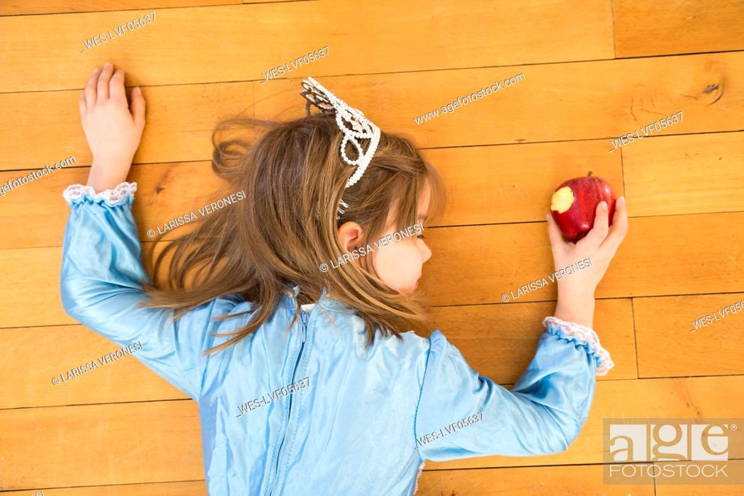 Stock Photo: Little girl lying on wooden floor holding bitten red apple.