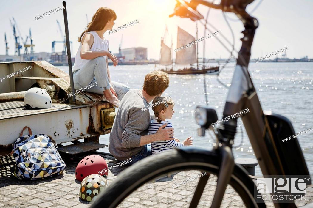Stock Photo: Germany, Hamburg, family having a break from a bicycle tour at River Elbe.