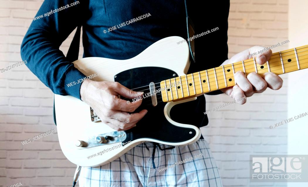 Imagen: Crop view of man playing electric guitar.
