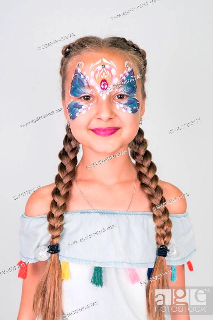 Stock Photo: Charming girl with a blue butterfly painted on her face.