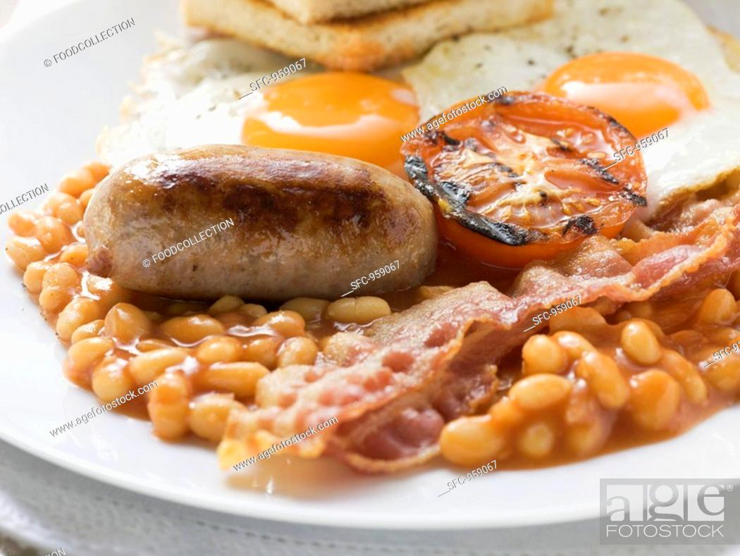Stock Photo: Baked beans, sausage, bacon, tomato, fried eggs and toast.