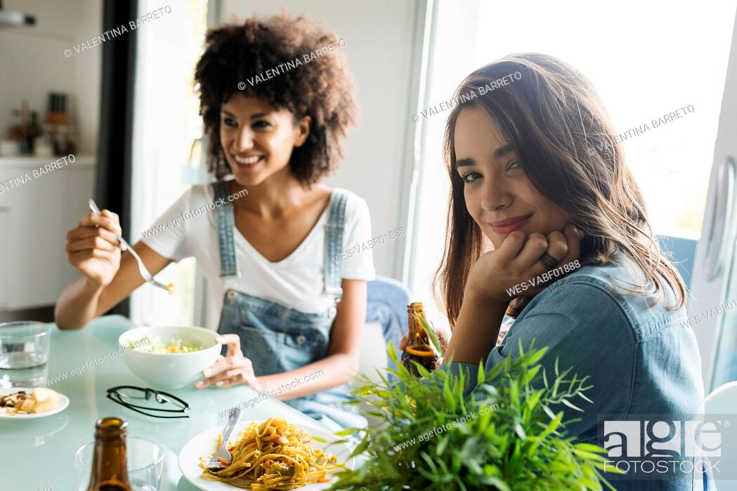 Photo de stock: Girlfriends sitting at table eating.