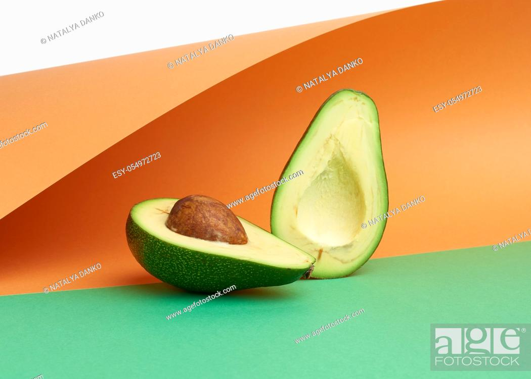 Stock Photo: half ripe green avocado with a brown bone on an abstract green-orange background with curved paper.