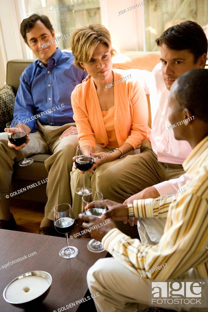 Stock Photo: Cheerful family having drinks in a house.