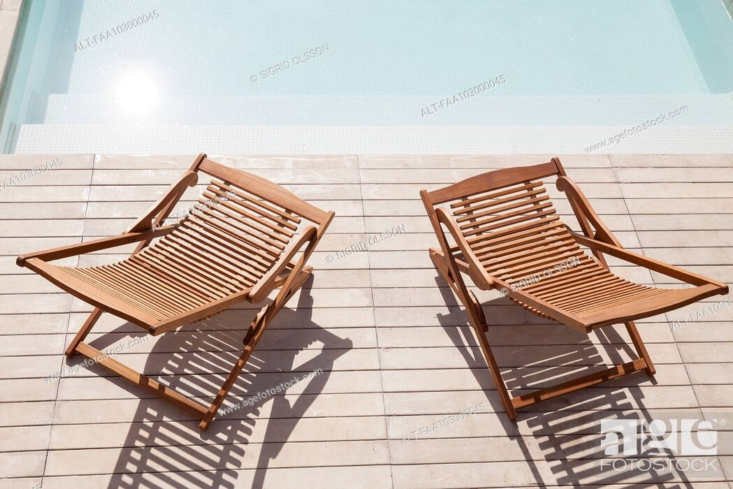 Stock Photo: Wooden deck chairs beside pool.