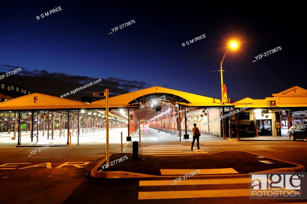Stock Photo: man walking at dusk through empty Queen Victoria Market, Melbourne.