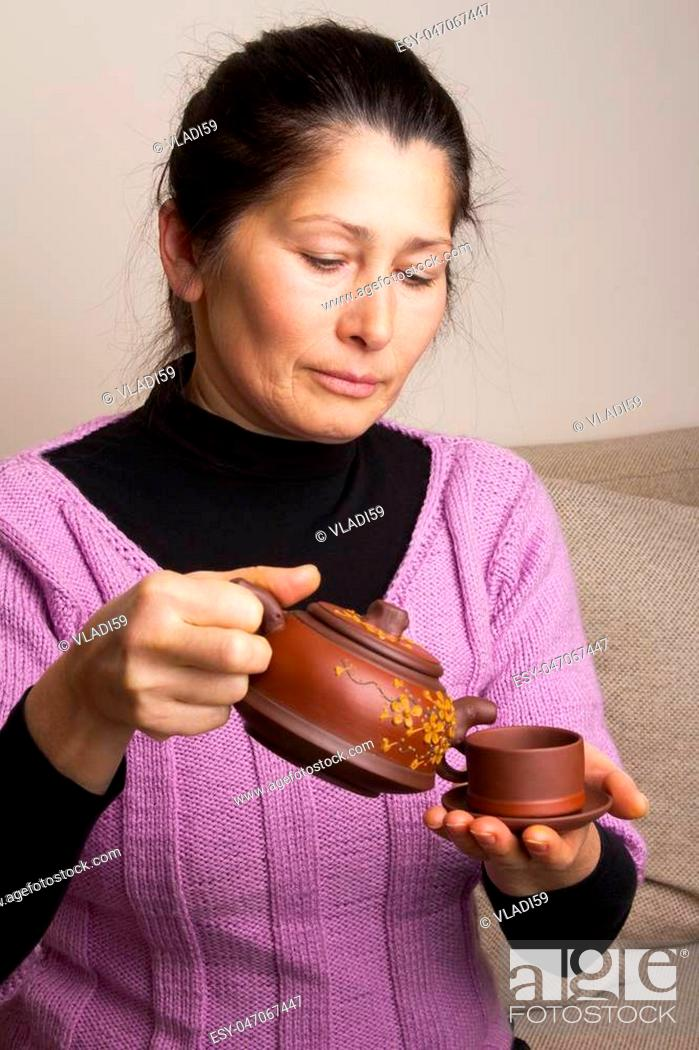 Stock Photo: Attractive senior woman pouring tea in cup at home.