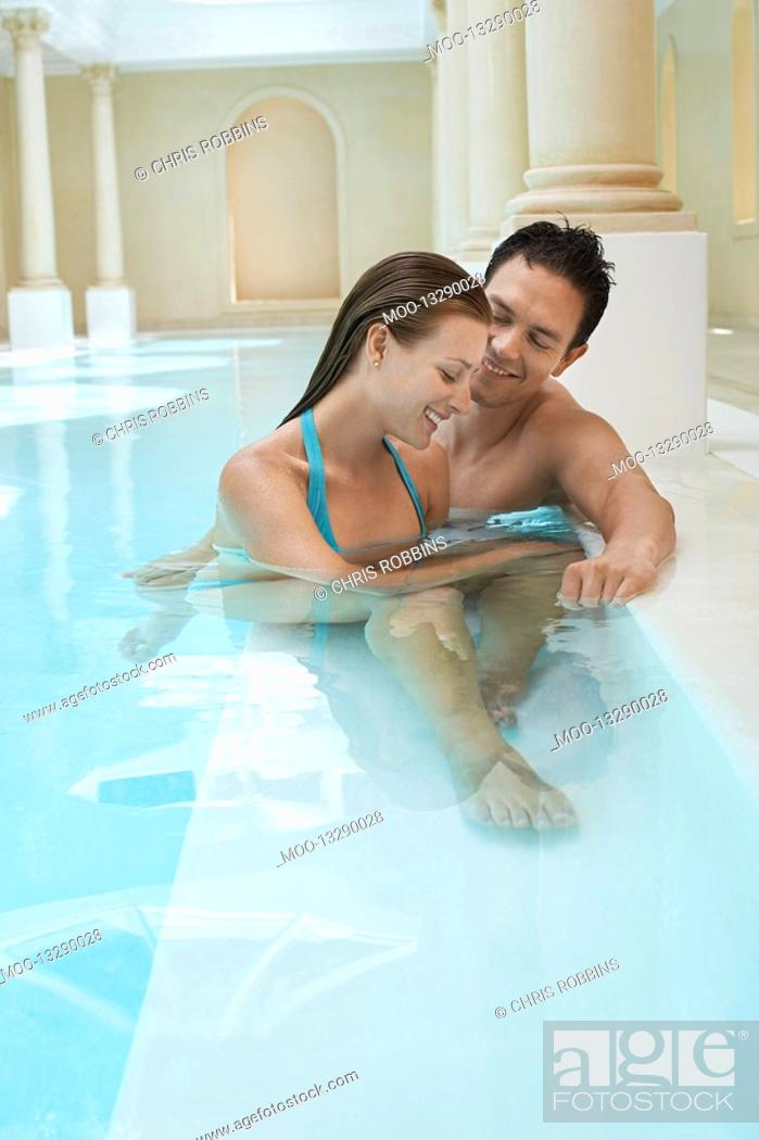 Stock Photo: Young couple talking at edge of swimming pool.