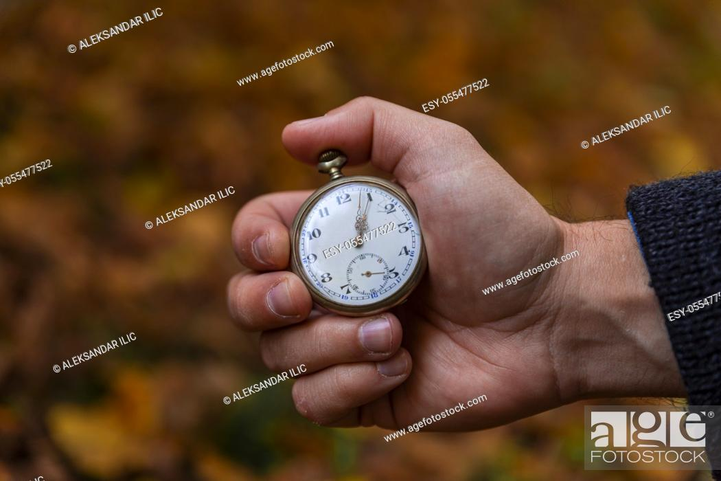 Stock Photo: Vintage Pocket watch in man's hand against the background of autumn dried brown leaves.