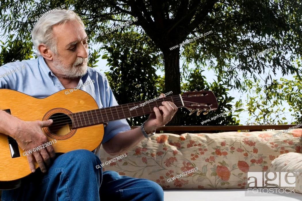 Stock Photo: Senior man sitting on a couch and playing a guitar.