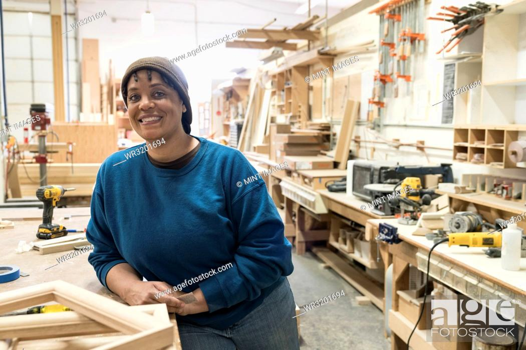 Stock Photo: Portrait of a Black woman carpenter in a large woodworking shop.